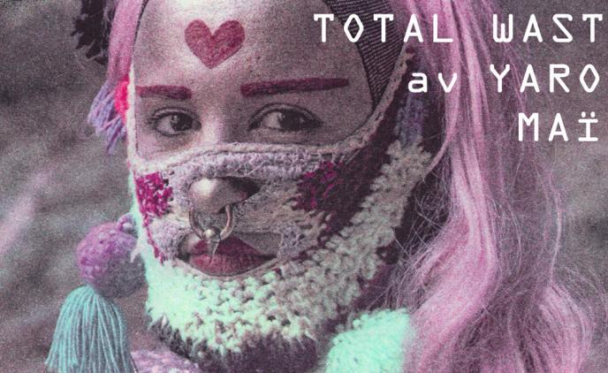 Självporträtt av konstnär Yaron Maim iklädd virkat skägg och lång rosa peruk.